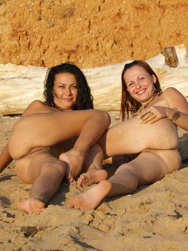 Обнаженная сучка сидит на берегу моря с сожительницой
