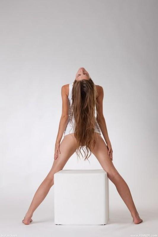 Лена растопырила ноги сидя на белоснежном кубе