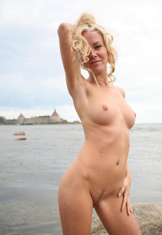 Возле крепости сидит голая блондинка