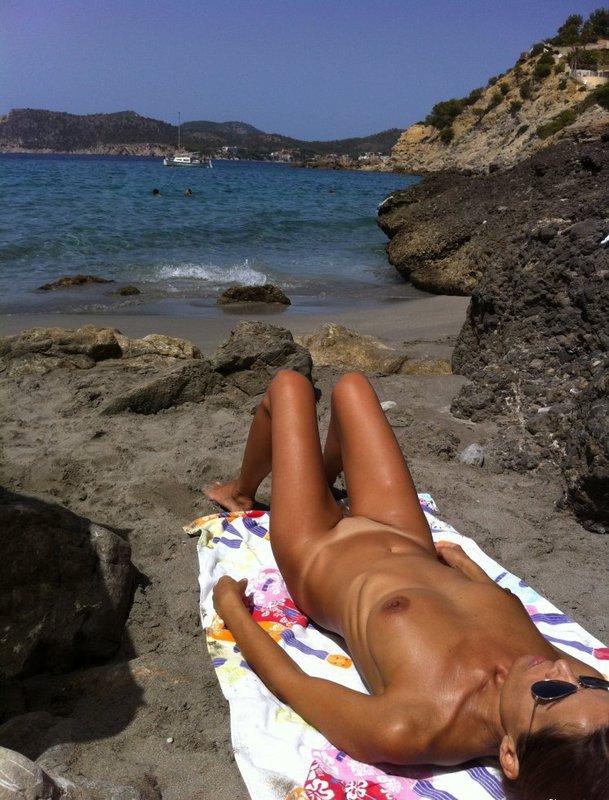 Костлявая тётя с маленькой грудью лежит под солнцем без нижнего белья