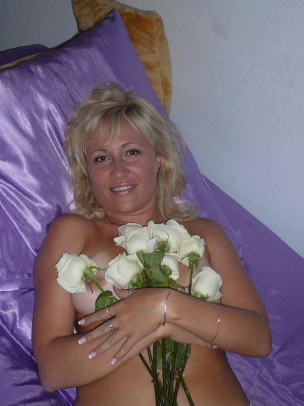 Блондинистая мамка обсыпала голое тело лепестками роз лежа на постели