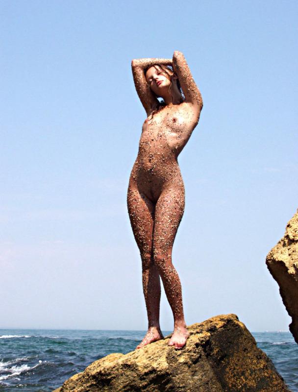 Морская фея голышом стоит под открытым небом