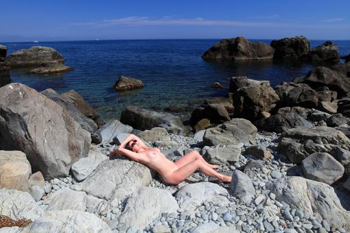 На камнях у моря голая зрелка хочет получить загар