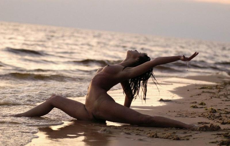 Нагая акробатка у воды встречает закат