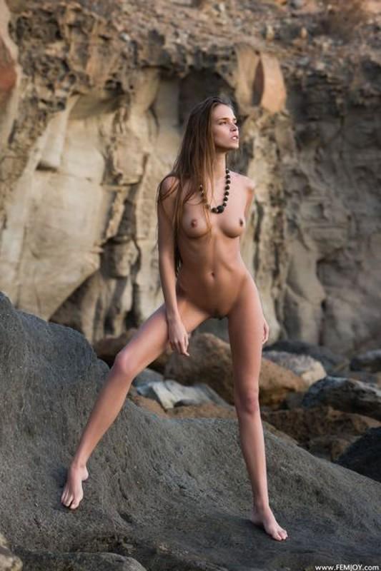 Длинноногая Симона позирует без одежды возле скалы