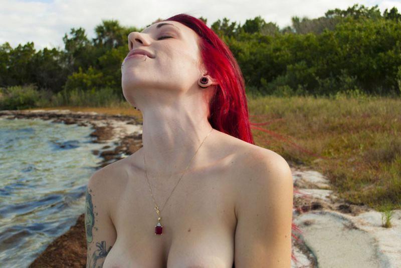 Красноволосая Эвора гуляет по берегу с оголенной грудью