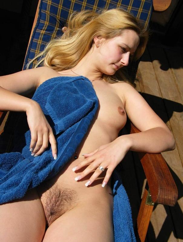 Модель со свелыми волосами на даче прикрыла обнаженная грудь синим полотенцем