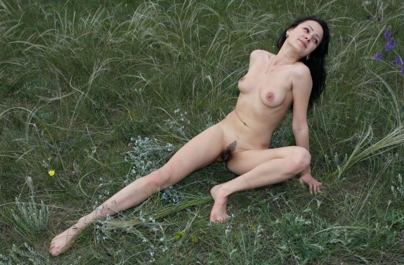 В траве с небритой мандой брюнетка наслаждается природой