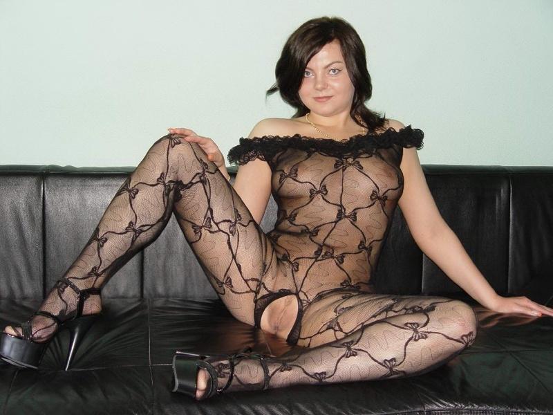 Зрелая женщина на черном диване хвастается киской