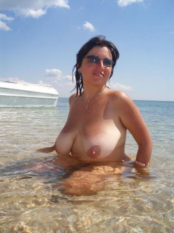 Зрелая нудистка плещется в морской воде