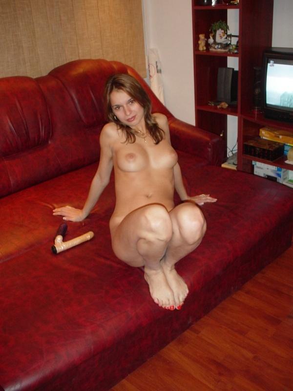 Голая няшка балуется с фаллоимитаторами сидя на диване