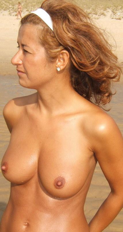 Зрелая дама с восхитительными сиськами показывает прелести на пляже