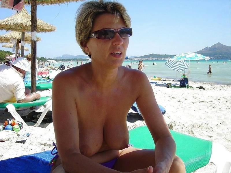 Женщина проводит время на пляже выставив на показ свои буфера