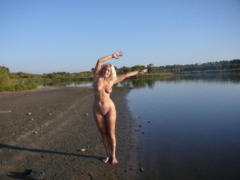 Зрелая дама светит нагим телом стоя на камне