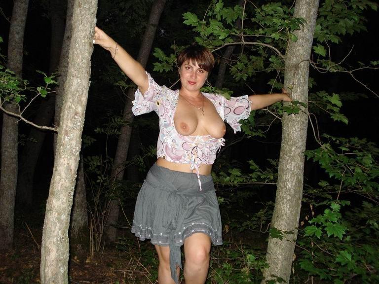 Взрослая женщина на аллее показывает манду под юбкой