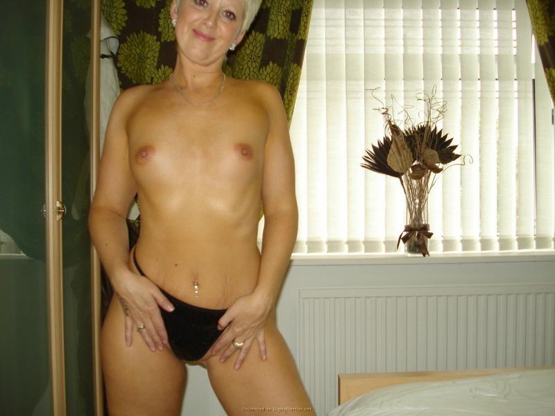 Зрелая блондинка в спальне светит маленькими сиськами