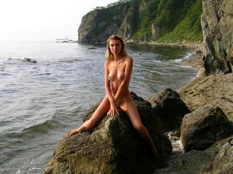 Голенькая бикса сидит на скале у моря