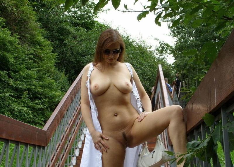 Стоя на мостике сисястая woman расстегнула светлый сарафан