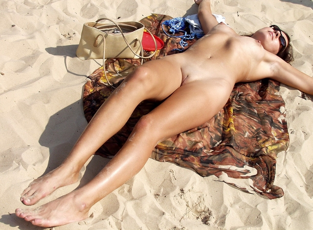 На пляже клевая нудистка загорает без купальника