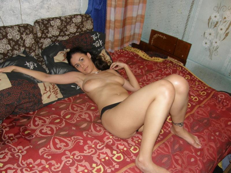 Шатенка лежит в кровати в одних бикини