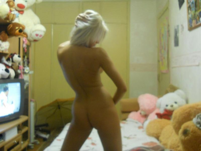 Красивая блондинка в спальне запечатлевает обнаженное тело