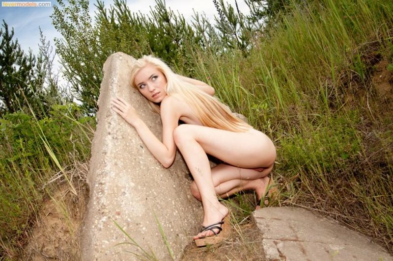 Раздетая светловолосая девушка в безлюдном месте обнимает камень