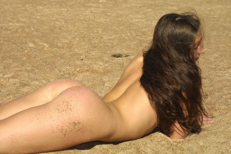 Обнаженная нудистка села попкой на песок