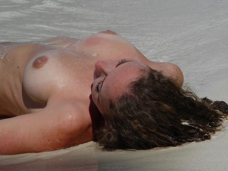 Кучерявая бикса сидит голышом на фоне моря