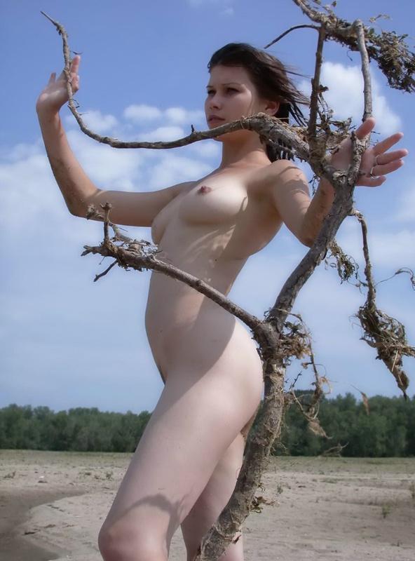 Раздетая няшка в саду позирует с веткой в руках секс фото
