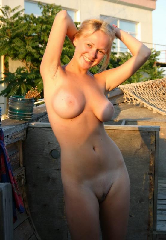 Красивая блондинка голышом встречает утро в деревне