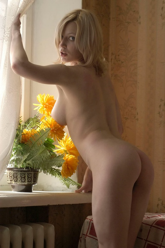 Нагая Оля подошла к комнатному цветку на подоконнике