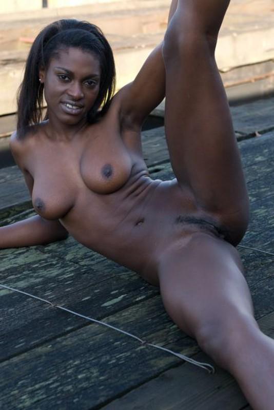 Негритянка на задворках показывает грудь и промежность