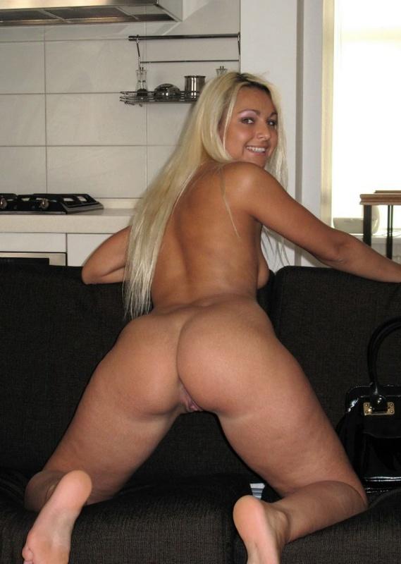 Чувственная шлюха на черном диване широко расстсавила ноги секс фото