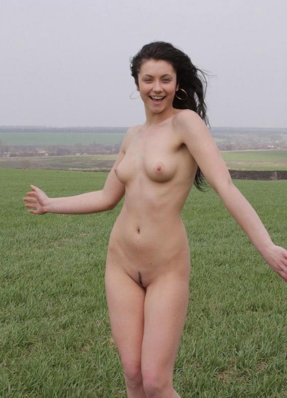 Голая брюнетка стоит босиком на зеленой траве