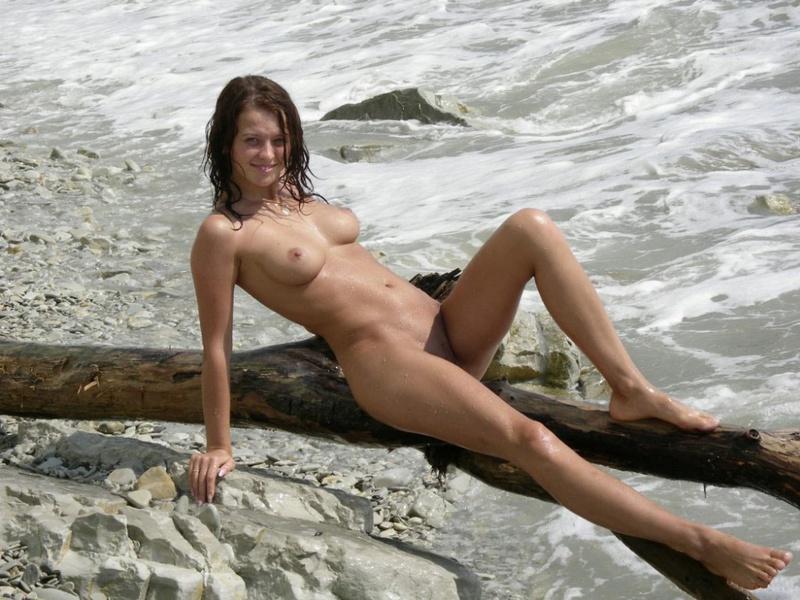 Обнаженная давалка стоит на берегу во время прибоя