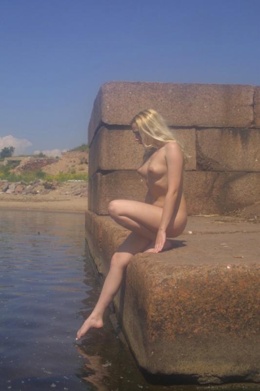Нагая блондиночка фоткается на каменных блоках