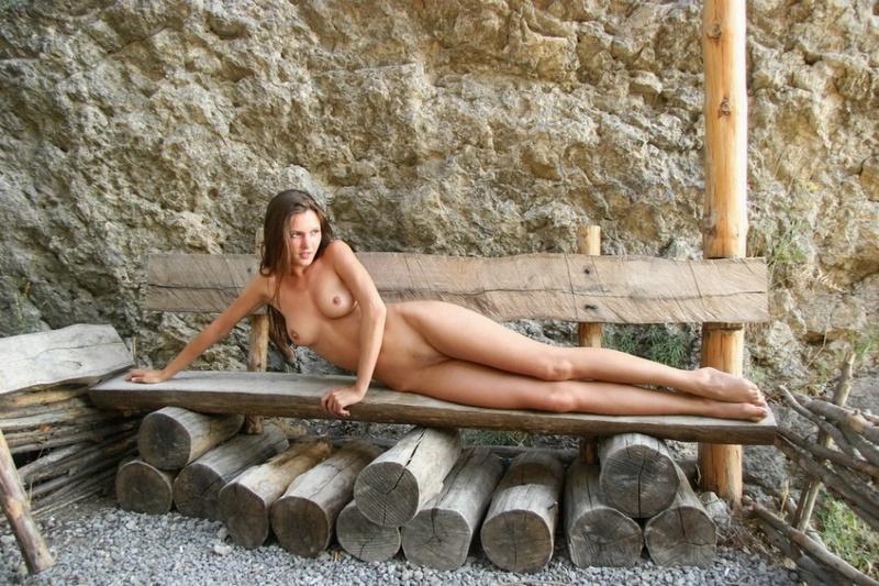 Привлекательная мадам фотографируется на скамейке без стрингов