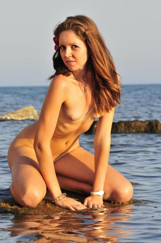 Молодая прелестница расставила ножки сидя на камне