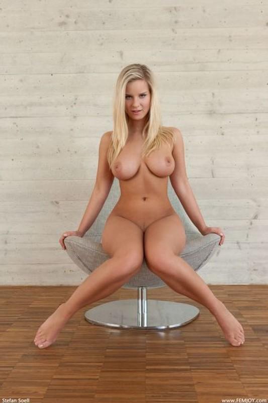 Великолепна сидит в кресле и хвастается объемным бюстом