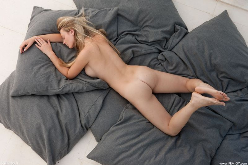 Кариша валяется на куче серых подушек