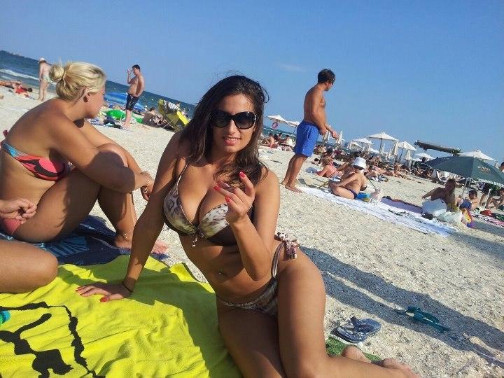 Девушка на пляже греет огромные сиськи
