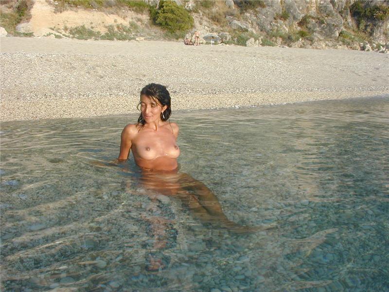 Сексуальна брюнетка голая отдыхает на берегу моря