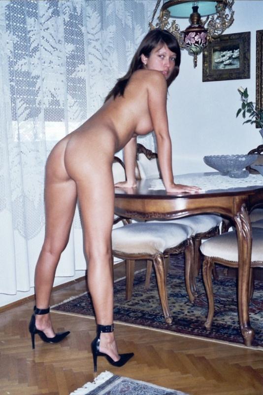 Нагая брюнеточка позирует на столе