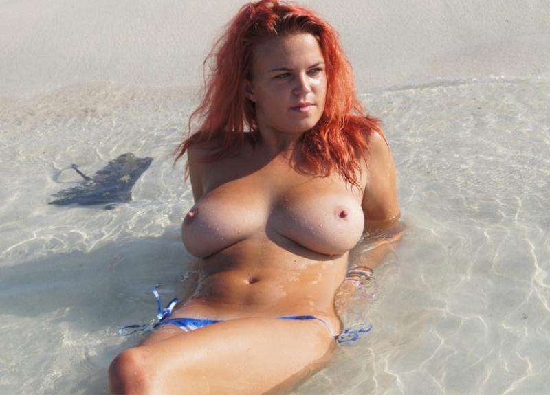 Рыжеволосая шалунья купается в бассейне в одних бикини
