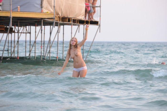 Баба плавает на песке без бюстгальтера