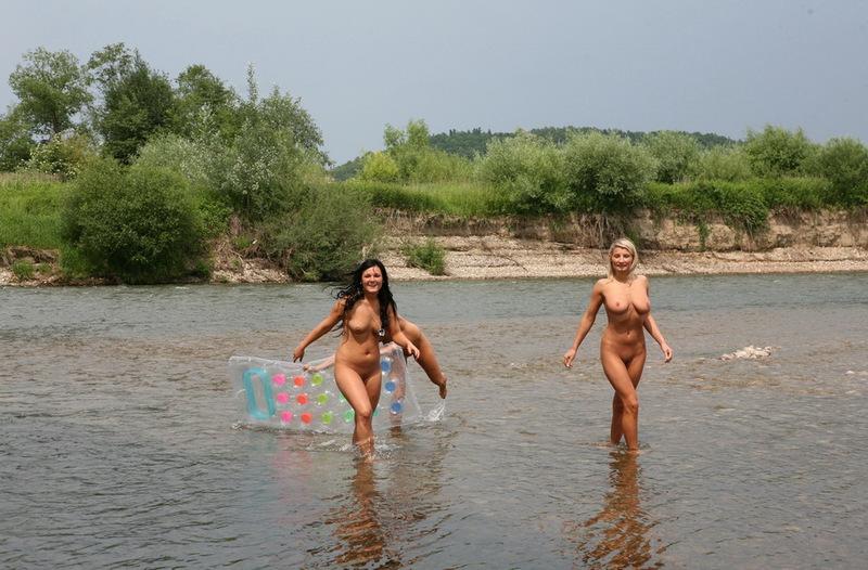 Нудистка обливает водой голые сиськи стоя в мелководной реке