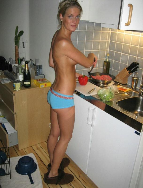 Матерая модель со свелыми волосами в одних трусиках готовит завтрак в домашних условиях