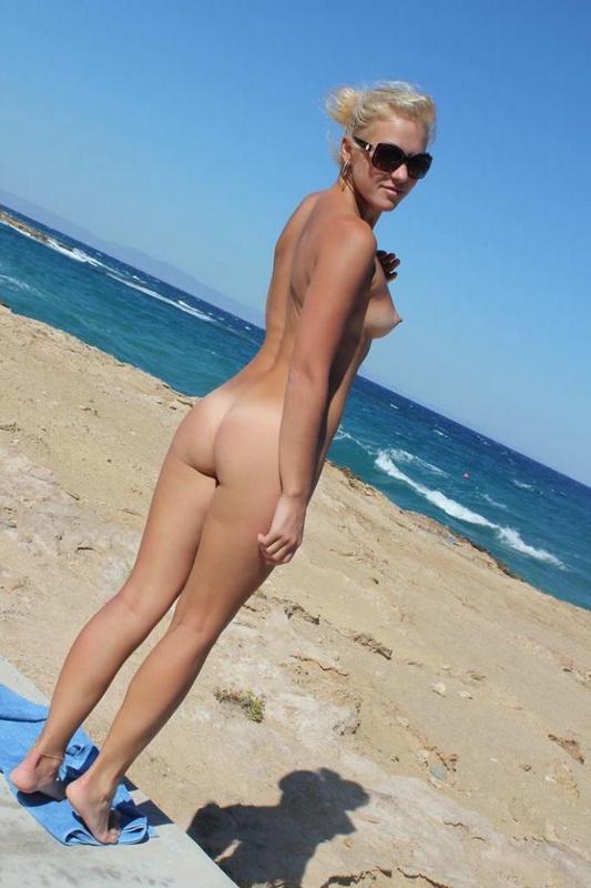 Голая блондинка сидит на бетонной плите возле моря