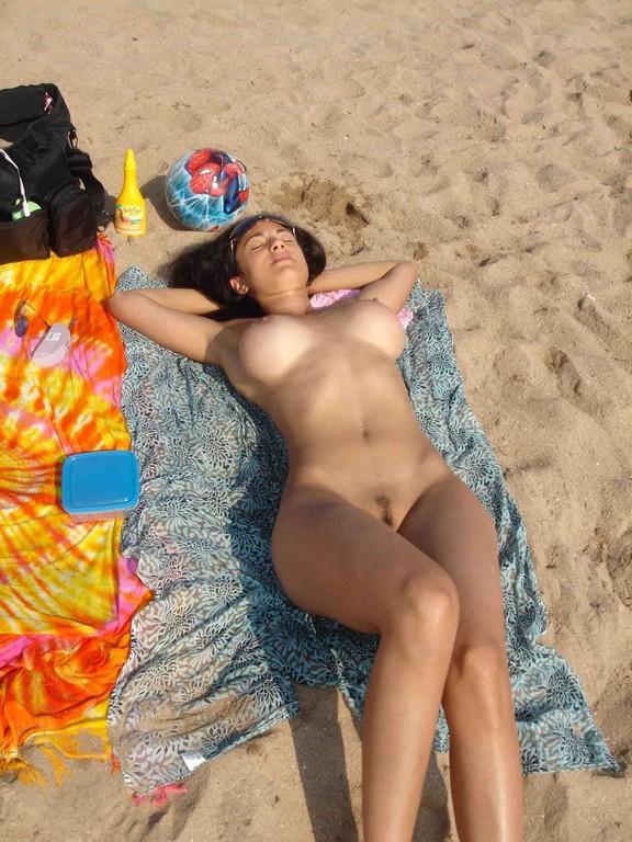 Полностью раздетая леди загорает на песке