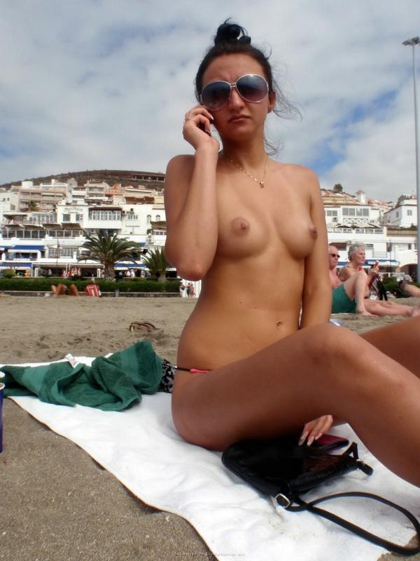 Брюнетка в розовых плавках отдыхает на пляже